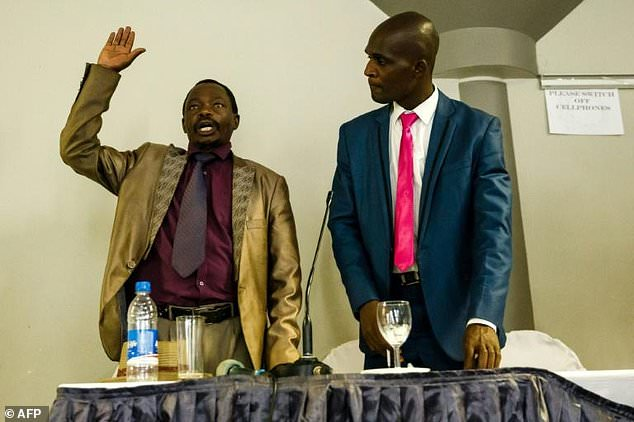 An eyewitness (L) takes an oath before giving his account of events to the head of a commission probing the August 1, 2018 post-poll violence in Zimbabwe which at least six people were shot dead by the military