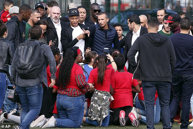 Locals crowd around Mbappe as he enjoys some time off during the international break