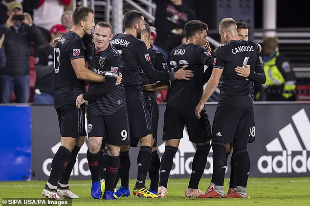 Rooney celebrates with his team-mates during their fourth straight victory, against Toronto