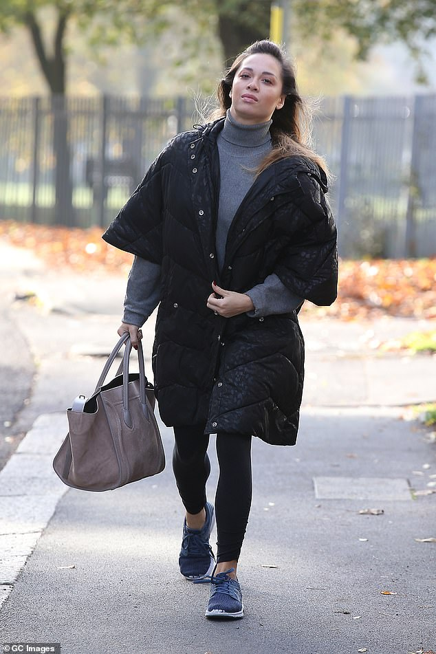 Warm: Katya covered up from the chilly weather in a large black padded cape-style jacket, worn over a grey turtleneck jumper and black leggings