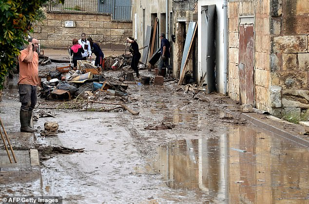 Locals inSant Llorenc des Cardassar earlier this week after water raced through the town, battering house and sweeping cars away