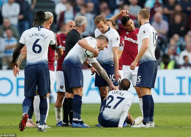 Lucas Moura (No 27) is on the end of a nasty-looking tackle as referee Martin Atkinson tries to deal with the situation