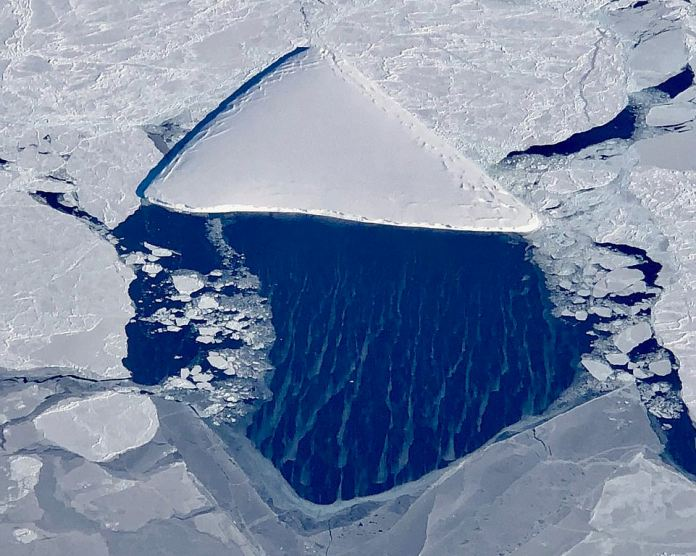 The 'pizzaberg': This berg resembles a slice of pizza. The Triangular iceberg surrounded by many different types of sea ice, off the Larsen ice shelf in the Weddell Sea. In the open water, grease ice is forming.