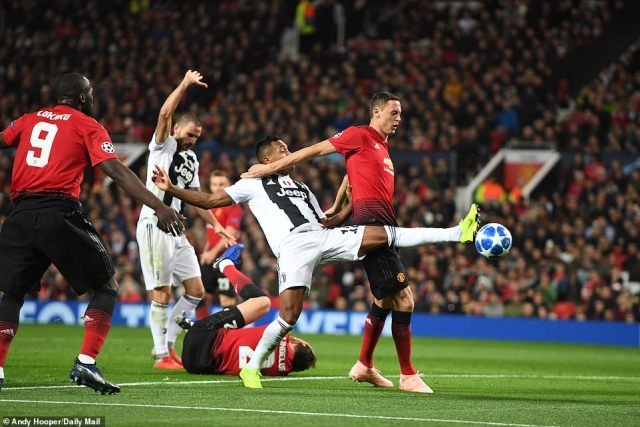 Juventus defender Alex Sandro stretches to get to the ball ahead of Nemanja Matic as Victor Lindelof lies holding his head