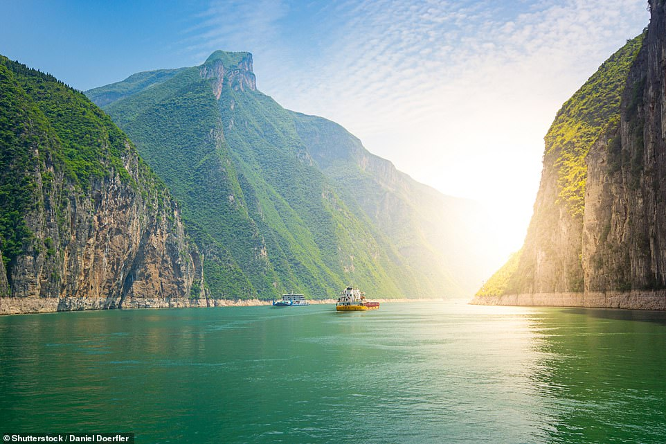 Two ships sail down the Yangtze River between breathtaking hills. The river is the longest in Asia and covers nearly 4,000 miles