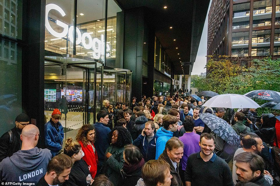 A large crowd is formed with people carrying umbrellas and braving the weather to walk out of Google in London on Thursday