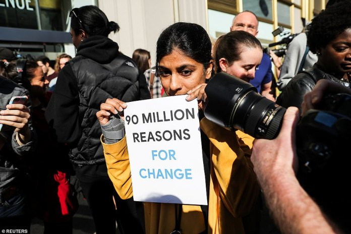 A New York Google employee carries a sign reading, '90 million reasons for change' during the walkout on Thursday