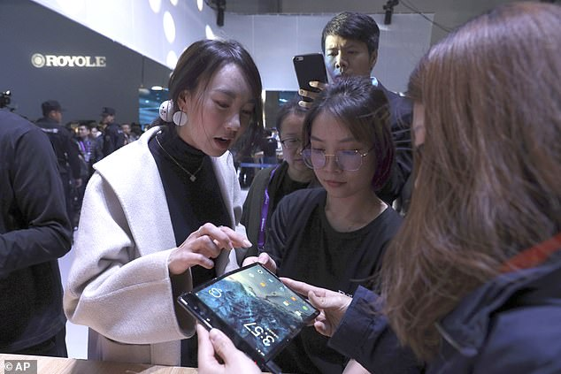 An interested customer tries to play with the bendy smartphone during the start in Beijing