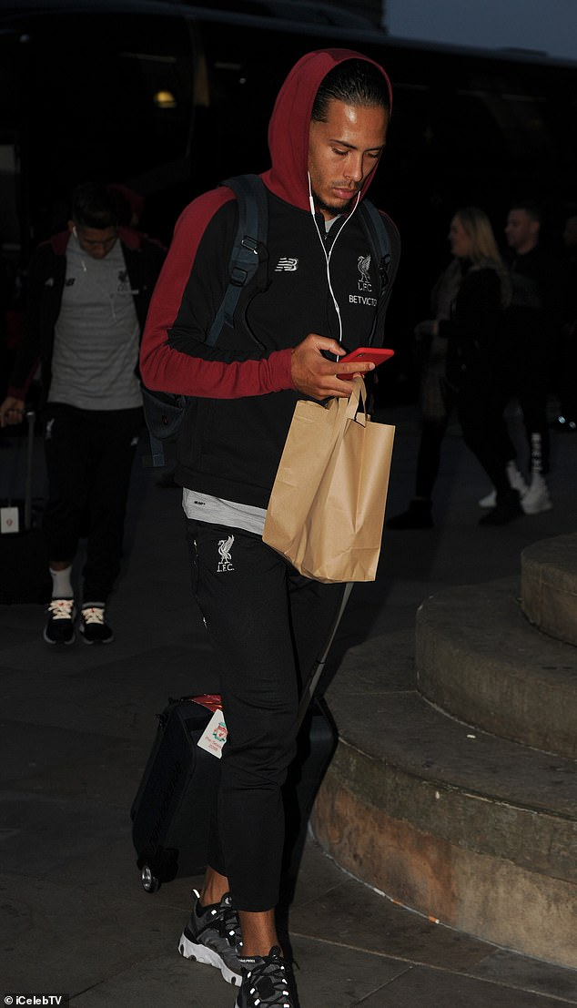 Virgil van Dijk held a paper bag as he texted on his arrival at Lime Street
