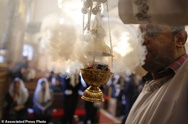 A priest spreads incense during the funeral for the slain Christians in the Church of the Great Martyr Prince Tadros in Minya, Egypt, Saturday, November 3, 2018. Coptic Christians in the Egyptian city of Minya were preparing to take their dead one day after the fighters to bury raids on three buses that brought Christian pilgrims on their way to a remote desert monastery. Seven people were killed and 19 were wounded. (AP Photo / Amr Nabil)