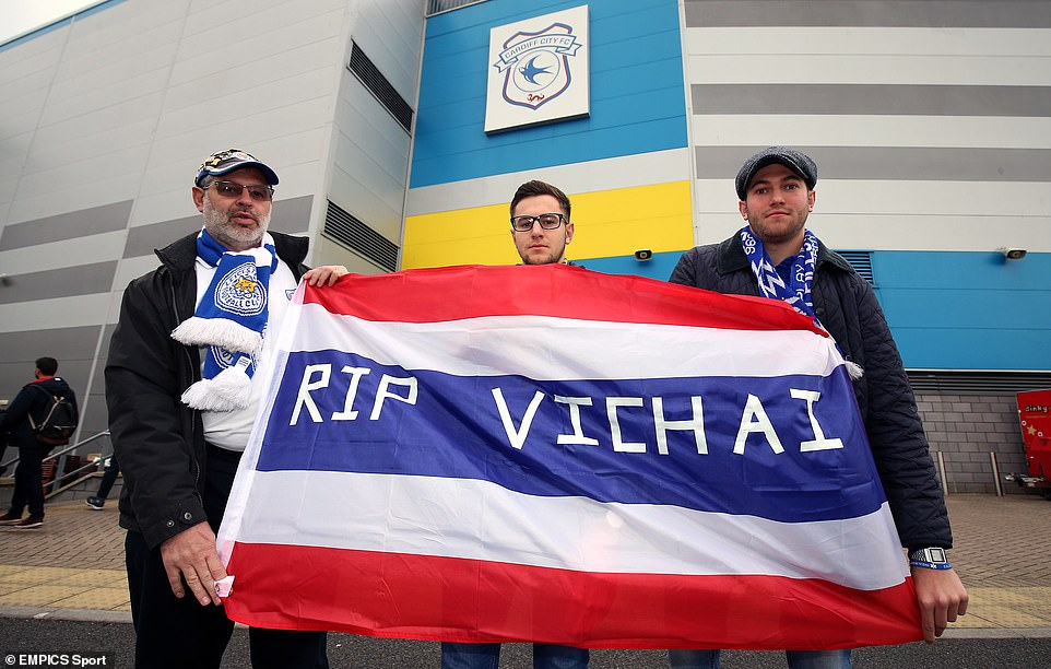 Three Leicester supporters show a flag of Thailand in front of the Cardiff City Stadium commemorating Srivaddhanaprabha