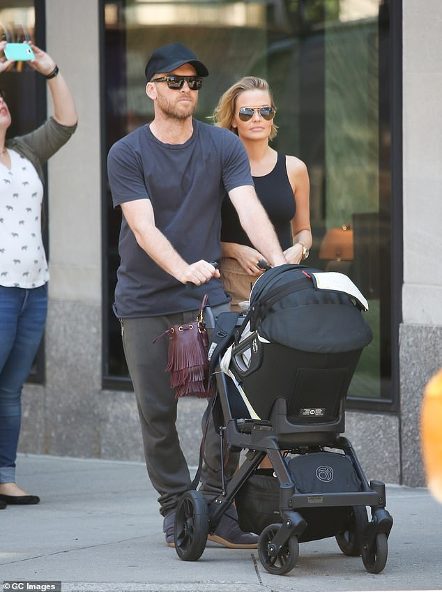 'You'll know if I'm pregnant again': Lara Bingle (right) denies she is expecting her third child with husband Sam Worthington (left) but reveals there's an unusual way fans can tell for sure that she's expecting