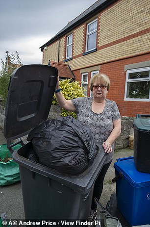 Sueorganising a vast array of recycling receptacles outside her detached home