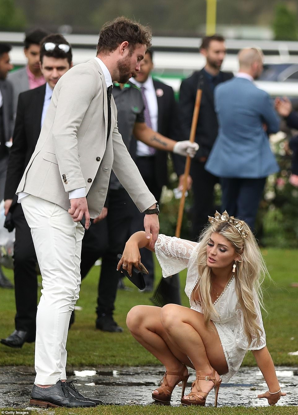 Racegoers stumble as they make their way home following the Melbourne Cup Day at Flemington Racecourse on Tuesday