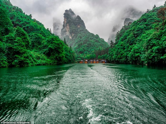 Fog swirls around the peaks of Wulingyuan Scenic Area in this wonderful photo taken by a tourist boat on a lake below