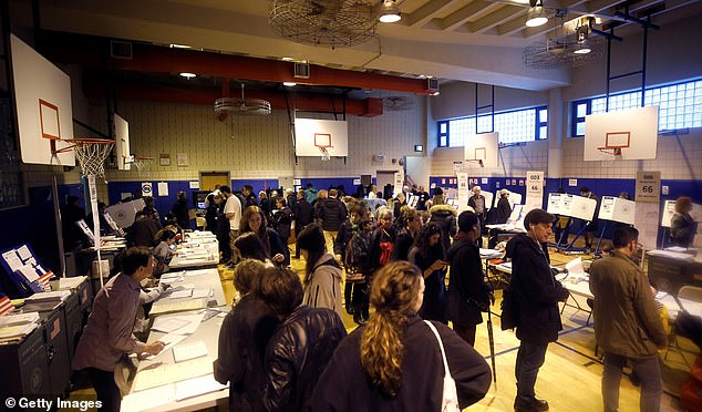 Turnout was so heavy at one packed precinct on Manhattan's Upper West Side that the line to scan ballots stretched around a junior high school gym on Tuesday morning