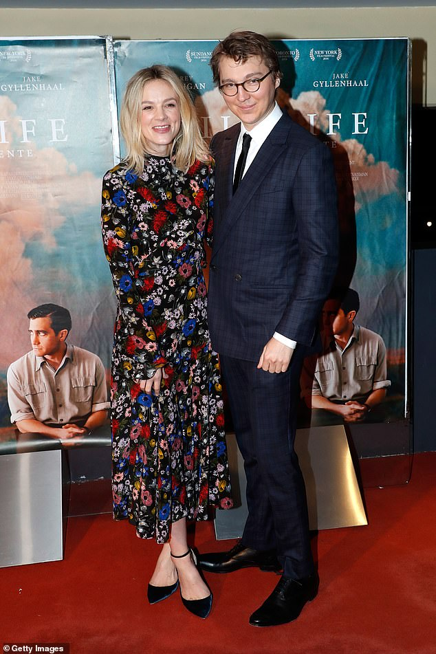 Stylish star: Carey looked lovely in the multicoloured brocade number, which she set off with cute blue velvet heels