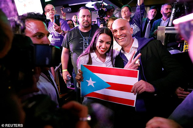 Ocasio-Cortez holds a Puerto Rico flag as she greets supporters at her midterm election night party in New York City