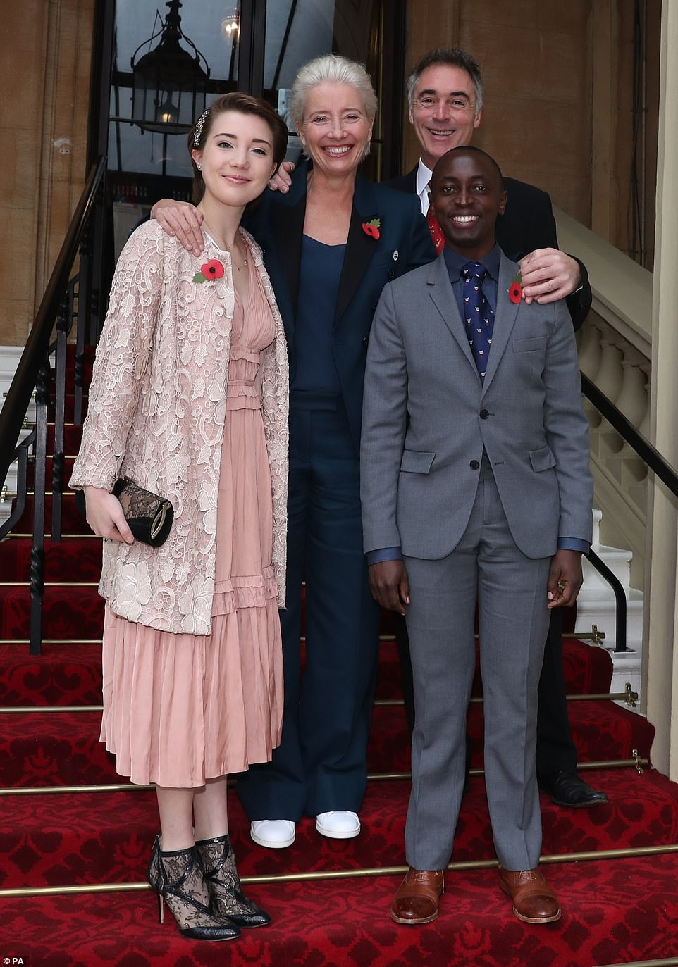 Radiant with pride: Emma continued her long list of successes at the Investiture ceremony Wednesday morning [pictured with husband Greg Wise and their children: Gaia, 18, and Tindyebwa]