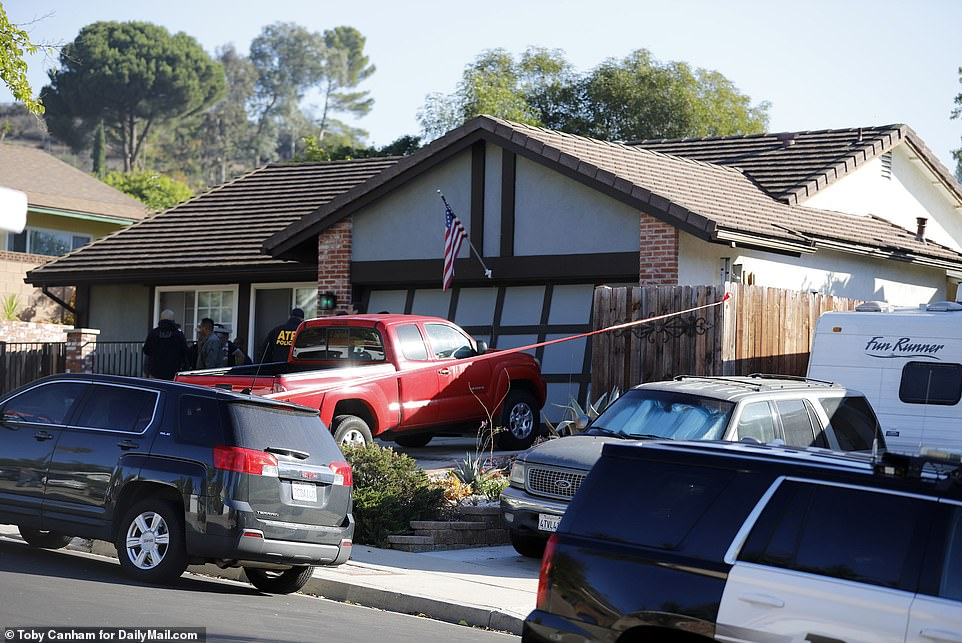 Police are seen outside Ian David Long's home in Newbury Park, near Thousand Oaks, on Thursday morning. His mother's red truck was parked in the driveway beneath an American flag draped from the garage. Their home is 5.5miles from the bar where the attack took place