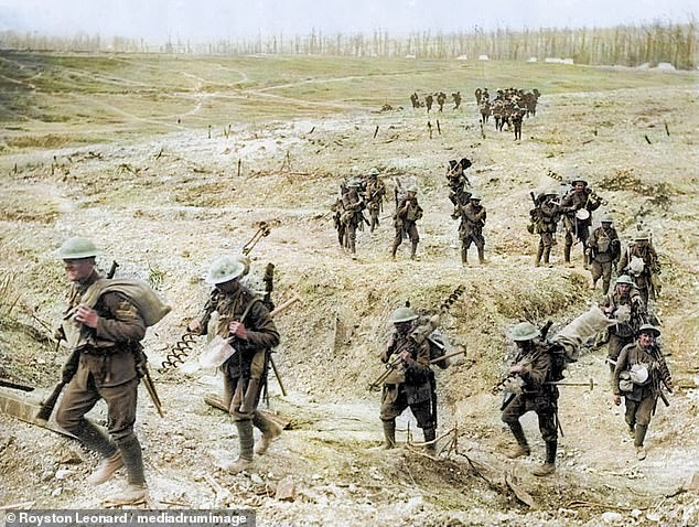 A colourised photograph originally taken during the conflict. A line of men walk across a bare slope, carrying all the gear needed to set up a new barbed-wire line. Many of the men are carrying tall metal posts shaped like corkscrews. These were used in the later part of the war as they could be screwed into the ground more quietly than straight posts could be hammered in