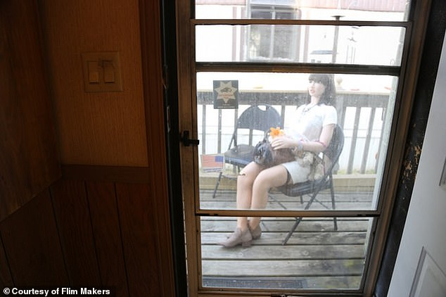 John's 'wife,' Jackie, sits on the porch outside of their small home; he takes great pride in dressing and often takes her on trips to the zoo or the couple's favorite restaurant