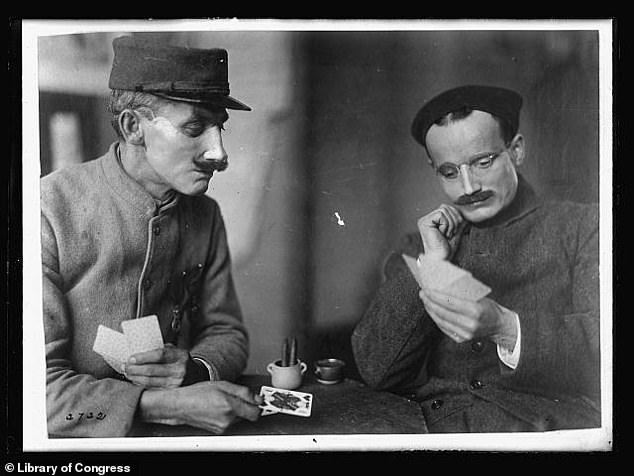 Two wounded soldiers played cards after applying full-face prosthetics in April 1919