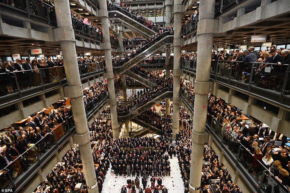 Plus tôt dans la journée, des membres du personnel avaient envahi l'atrium lors de la cérémonie de commémoration de l'Armistice du jour du Souvenir à Lloyds of London, en photo.