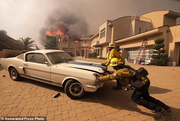 Firefighters push a car from home to Malibu Lake in Malibu, Calif., Friday, Nov. 9, 2018. (AP Photo / Ringo H.W. Chiu)