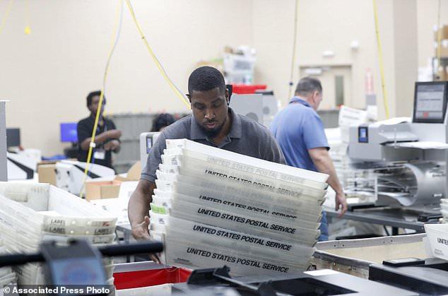 Ein Angestellter im Broward County Supervisor of Elections-Büro sammelt Mins mit Stimmzetteln, während er Stimmzettel aus den Zwischenwahlen am Donnerstag, 8. November 2018, in Lauderhill, Florida (AP Foto / Wilfredo Lee) zählt.
