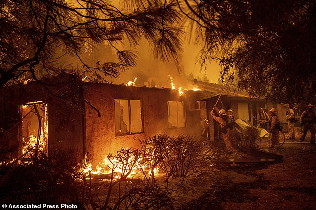 Feuerwehrleute sorgen dafür, dass sich die Flammen nicht durch den Apartmentkomplex Shadowbrook ausbreiten, als am Freitag, dem 9. November 2018, im Paradise, Kalifornien, ein Lauffeuer brennt. (AP Photo / Noah Berger)