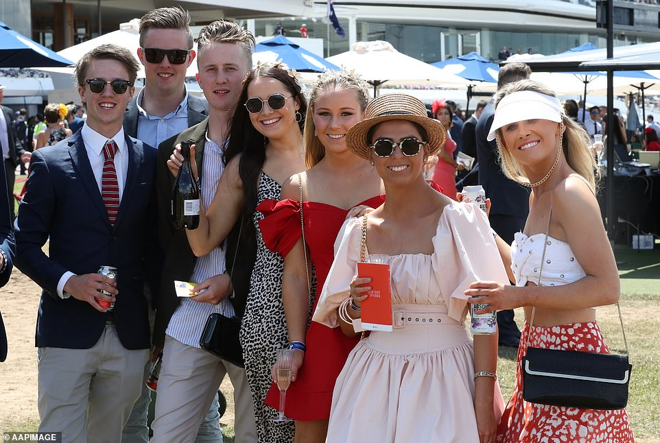 A group of fashionably dressed racegoers show off the wide selection of beverages available at the event