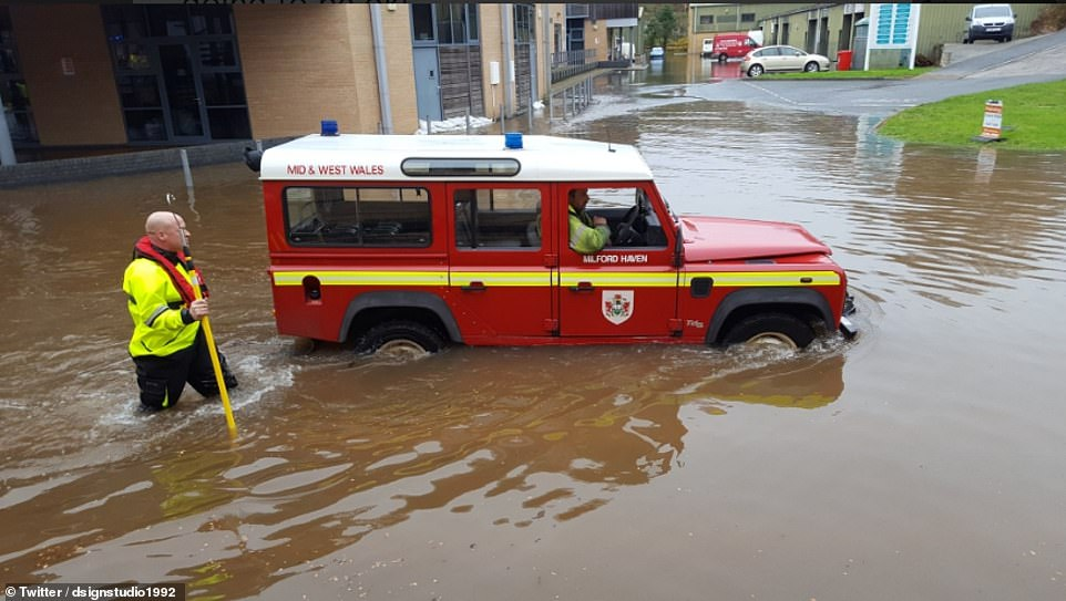 Emergency teams wearing life jackets in Milford Haven were seen driving along the streets in vehicles after the rain caused the streets to flood