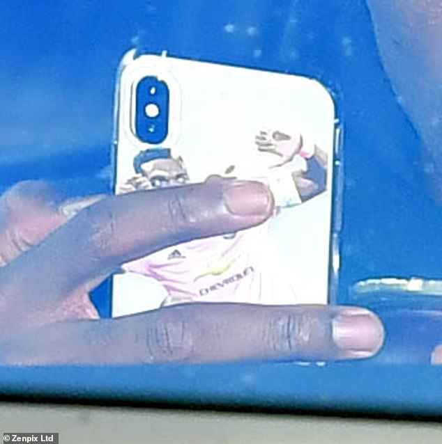 The midfielder glanced at his cell phone case, which was decorated with a picture of him