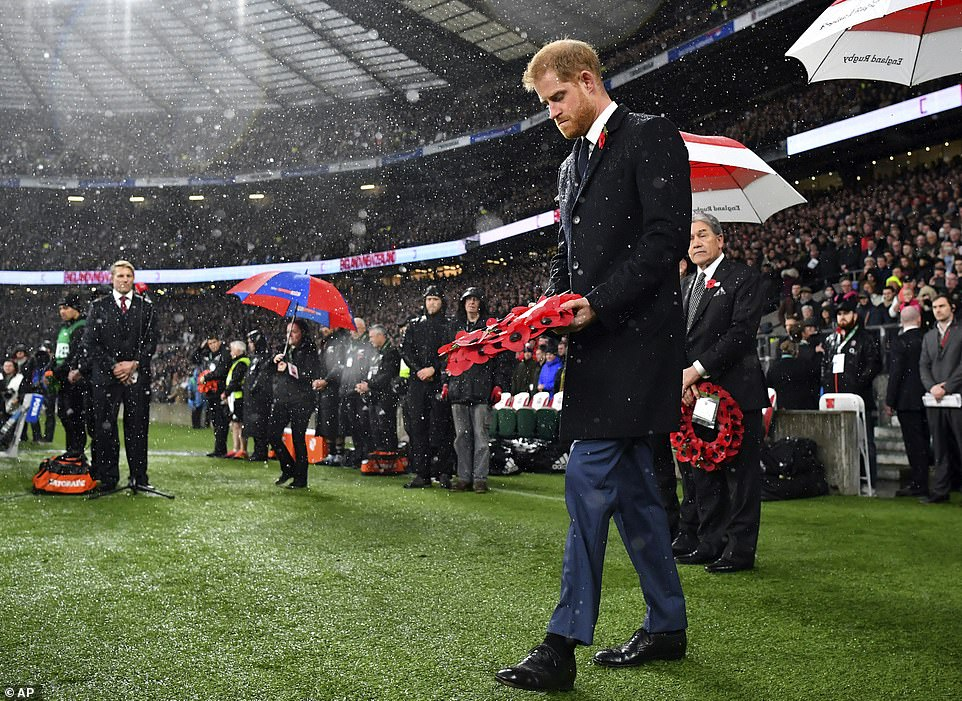 Britain's Prince Harry carries a wreath during a ceremony to commemorate 100 years since the end of the First World War, before watching the international rugby match between England and New Zealand