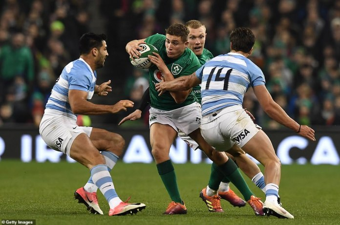 The Irishman Jordan Larmour tries to push forward but is tackled by the Argentine Delguy