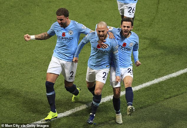 David Silva (centre) wheels away in celebration after opening the scoring against rivals United