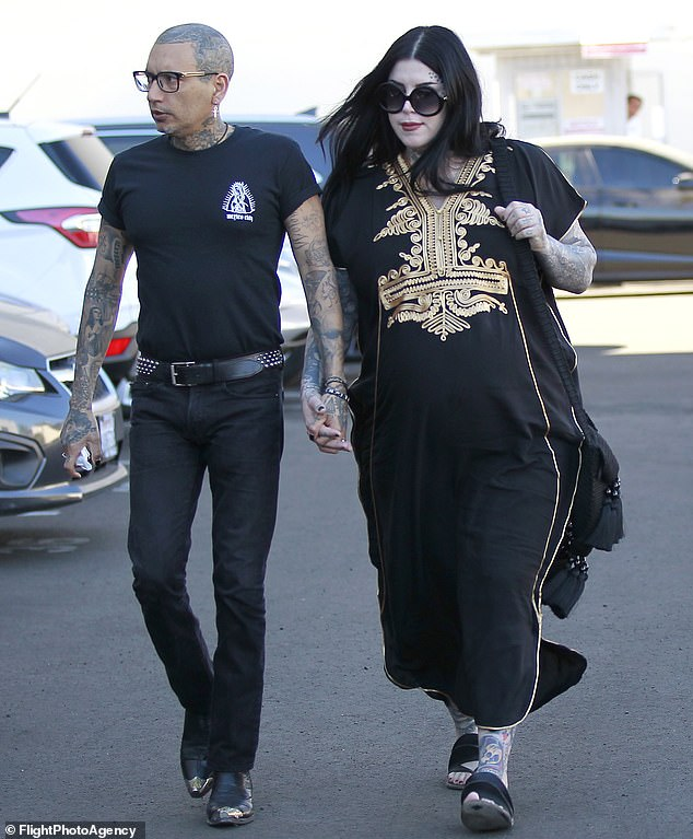 Glamour gothique! La mère devrait habiller son renflement avec une robe longue noire et dorée avec des sandales plates