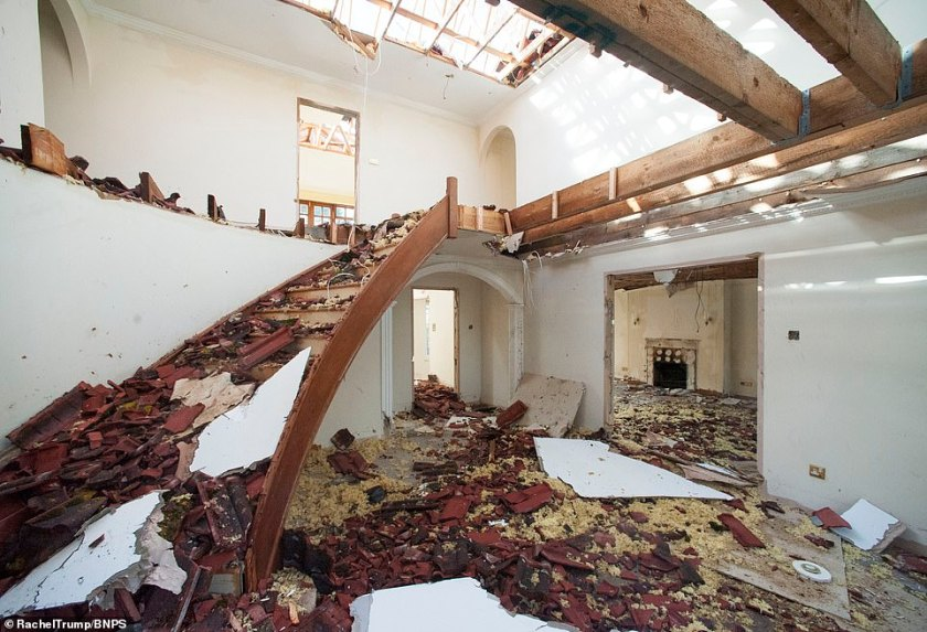 Debris from the destruction of the roof and ceiling scattered all over the lobby area of the former luxury mansion in Poole
