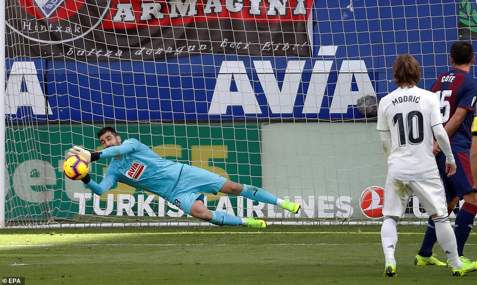 Eibar goalkeeper Asier Riesgo gets down well and dives to his left to palm an effort from a Madrid player away from goal