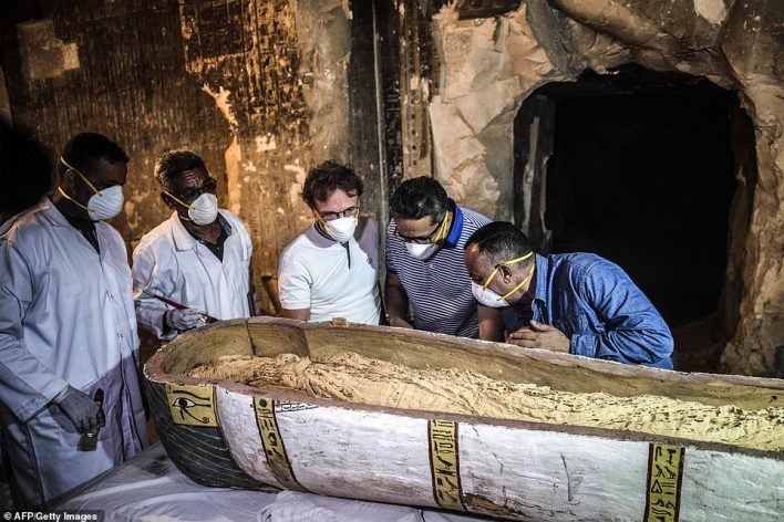 Egypt's Antiquities Minister Khaled el-Enany (centre) and Mostafa Waziri (right), the Secretary General of the Supreme Council of Antiquities, inspect an intact sarcophagus