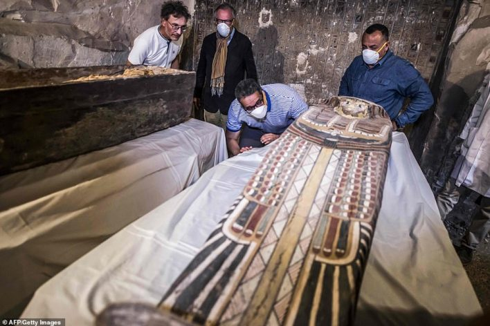 Egypt's Antiquities Minister Khaled el-Enany (centre) and Mostafa Waziri (right), the Secretary General of the Supreme Council of Antiquities, inspect an intact sarcophagus during its opening at Al-Assasif necropolis