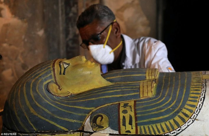 An archaeologist removes the cover of an intact sarcophagus inside the tomb TT33 in Luxor, Egypt