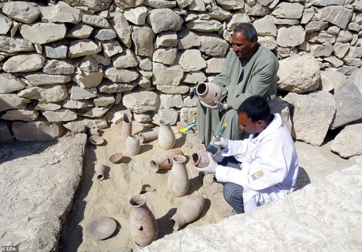 Egyptian archaeologists work on restoring pottery including plates and vases outside the newly discovered tomb at al-Assassif Necropolis