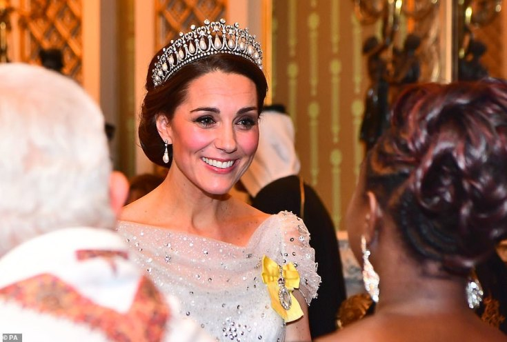 The Duchess of Cambridge accessorised with a favourite pair of pearl drop earrings and proudly wore the yellow ribbon of the Queen's Royal Order pinned to her chest