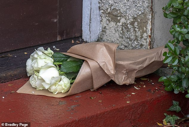 A shocked neighbour left these white roses on Mrs Whale's doorstep today