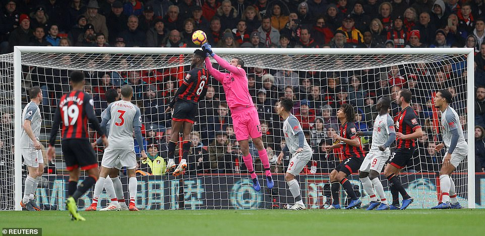 Liverpool goalkeeper Alisson rises highest to punch away the cross as Jefferson Lerma looks to get his head on the ball