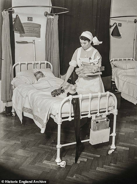 More than a year into the war in 1940, another photograph shows a nurse at St Bartholomews Hospital in West Smithfield, laying out gifts at the end of her patient's bed ready for them to wake on Christmas morning