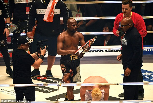 Mayweather celebrates with his trophy as his opponent is left on his haunches on the canvas