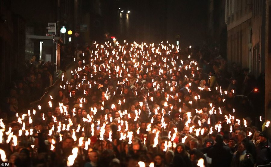 People take part in a torchlight procession along the Royal Mile in Edinburgh during Hogmanay celebrations yesterday
